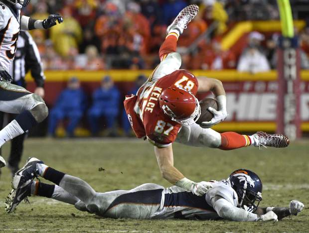 Kansas City Chiefs tight end Travis Kelce (87) is brought down by Denver Broncos safety Darian Stewart (26) during the second half of an NFL football game in Kansas City, Mo., Sunday, Dec. 25, 2016. (AP Photo/Ed Zurga)