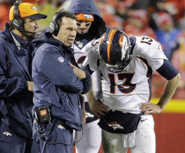 Denver Broncos head coach Gary Kubiak talks to quarterback Trevor Siemian (13) during the first half of an NFL football game against the Kansas City Chiefs in Kansas City, Mo., Sunday, Dec. 25, 2016. (AP Photo/Charlie Riedel)