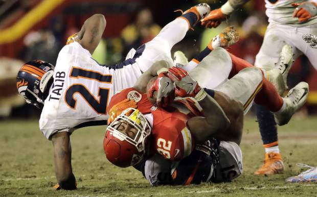 Kansas City Chiefs running back Spencer Ware (32) is tackled by Denver Broncos linebacker Todd Davis, bottom, and cornerback Aqib Talib (21) during the second half of an NFL football game in Kansas City, Mo., Sunday, Dec. 25, 2016. (AP Photo/Charlie Riedel)