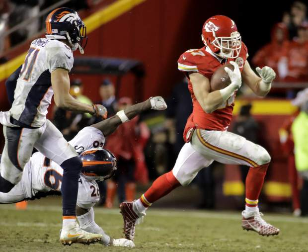 Kansas City Chiefs tight end Travis Kelce (87) carries the ball away from Denver Broncos safety Darian Stewart (26) and safety Justin Simmons (31) during the second half of an NFL football game in Kansas City, Mo., Sunday, Dec. 25, 2016. (AP Photo/Charlie Riedel)