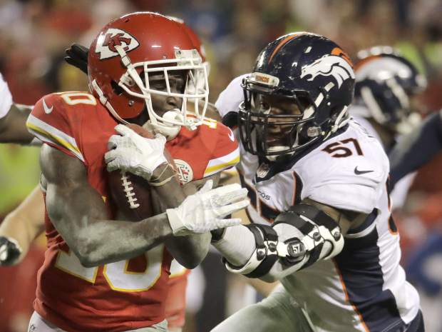 Kansas City Chiefs wide receiver Tyreek Hill (10) runs away from tackle attempts by Denver Broncos linebacker Shaquil Barrett and linebacker Dekoda Watson (57) during the second half of an NFL football game in Kansas City, Mo., Sunday, Dec. 25, 2016. (AP Photo/Charlie Riedel)