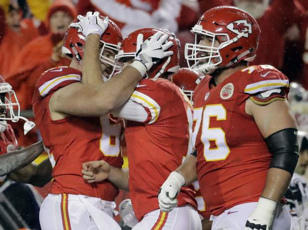 Kansas City Chiefs quarterback Alex Smith, second right, celebrates his touchdown against the Denver Broncos with offensive lineman Mitch Morse, left, and offensive lineman Laurent Duvernay-Tardif (76) during the first half of an NFL football game in Kansas City, Mo., Sunday, Dec. 25, 2016. (AP Photo/Charlie Riedel)