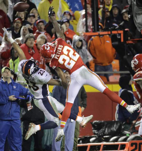 Kansas City Chiefs defensive back Marcus Peters (22) and Denver Broncos running back Devontae Booker (23) can't reach a pass during the second half of an NFL football game in Kansas City, Mo., Sunday, Dec. 25, 2016. (AP Photo/Charlie Riedel)