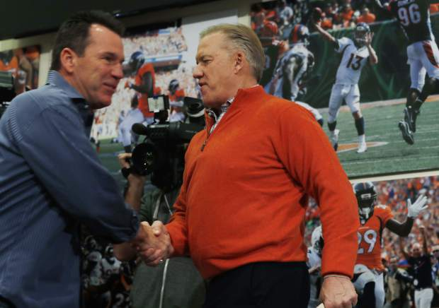 Gary Kubiak, left, shakes hands with Denver Broncos general manager John Elway as Kubiak heads to the podium to step down as head coach of the Broncos because of health concerns on Monday.