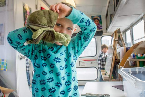 August Freund plays with a turtle puppet during his morning preschool class on Gus the Bus.