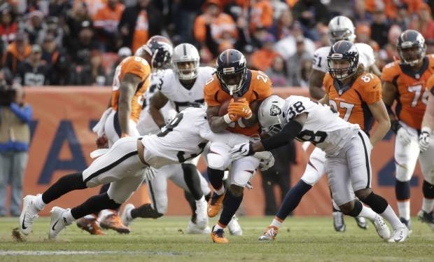 Denver Broncos running back Justin Forsett (20) breaks tackle attempts by Oakland Raiders strong safety T.J. Carrie, right, and strong safety Keith McGill, lower left, on a 64-yard run during the first half of an NFL football game, Sunday, Jan. 1, 2017, in Denver. (AP Photo/Jack Dempsey)