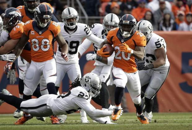 Denver Broncos running back Justin Forsett (20) avoids a tackle from Oakland Raiders free safety Reggie Nelson, lower left, while making a 64-yard run in the first half of an NFL football game, Sunday, Jan. 1, 2017, in Denver. (AP Photo/Jack Dempsey)