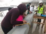 Arianna Hernandez, Cami Vizcaino, Herica Martinez and Veronica Geronimo take turns signing the beam during Thursday's topping out ceremony for the new Riverview School.