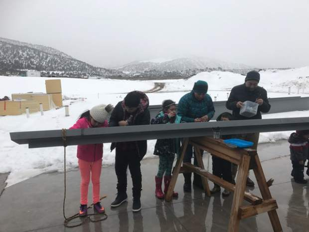 Multiple people, including would-be future students, showed up despite the cold and wet weather to sign the beam during a topping out ceremony last Thursday on location at the new Riverview School south of Glenwood Springs.