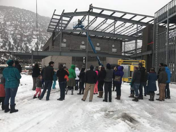 A gathering of people watch as the last beam is lifted into place during Thursday's topping out ceremony on location of the new Riverview school south of Glenwood Springs.
