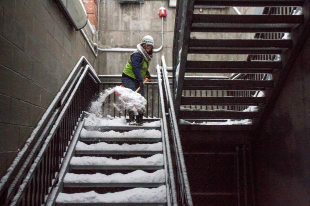 City of Glenwood Springs worker Staci Andrassy works to keep up with shoveling the walkways and stairs around the Ninth street parking garage after the recent snowstorms.
