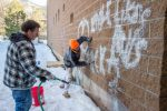 Bob Harrison, left, and Jesus Sanchez work to clean off the graffiti found on the north side of the Glenwood Springs High School building.