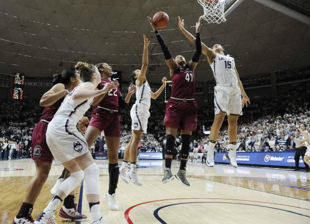 South Carolina's Alaina Coates, center, pulls down a rebound between Connecticut's Napheesa Collier and Connecticut's Gabby Williams, right, in the first half of an NCAA college basketball game, Monday, Feb. 13, 2017, in Storrs, Conn. (AP Photo/Jessica Hill)