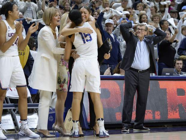 Connecticut head coach Geno Auriemma, right, reacts as Connecticut's Gabby Williams (15) is congratulated by associated head coach Chris Dailey and embraced by assistant coach Marisa Moseley at the end of an NCAA college basketball game against South Carolina, Monday, Feb. 13, 2017, in Storrs, Conn. UConn won their 100th straight game. (AP Photo/Jessica Hill)