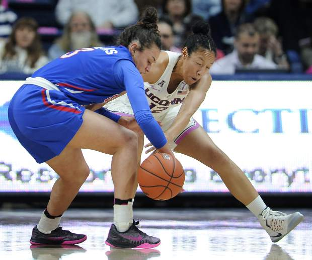 SMU's McKenzie Adams, left, and Connecticut's Saniya Chong, right, battle for control of the ball in the first half of an NCAA college basketball game, Saturday, Feb. 11, 2017, in Storrs, Conn. (AP Photo/Jessica Hill)