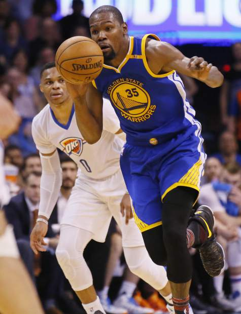 Golden State Warriors forward Kevin Durant (35) drives past Oklahoma City Thunder guard Russell Westbrook, left, in the second quarter of an NBA basketball game in Oklahoma City, Saturday, Feb. 11, 2017. (AP Photo/Sue Ogrocki)