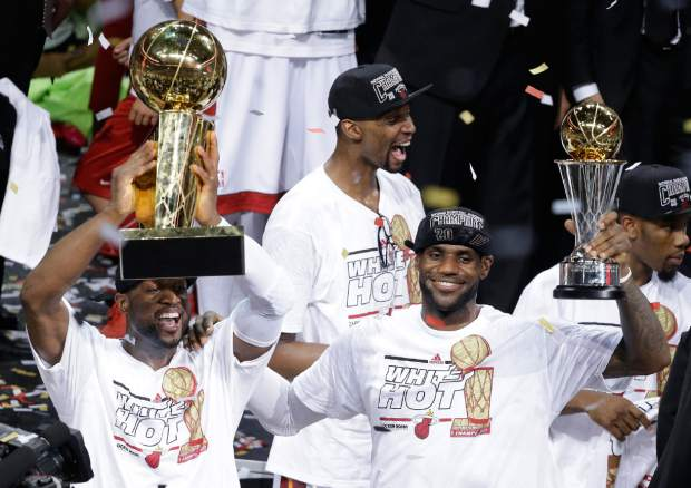 FILE - In this June 21, 2013, file photo, the Miami Heat's Dwyane Wade, left, holds the Larry O'Brien NBA Championship Trophy as LeBron James holds his Bill Russell NBA Finals Most Valuable Player Award and Chris Bosh, top, reacts after Game 7 of the NBA basketball championship against the San Antonio Spurs, in Miami. There have been superteams that found winning formulas, like Miami when James and Bosh joined Wade. (AP Photo/Wilfredo Lee, File)