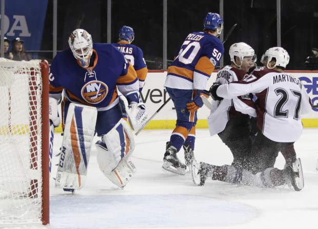 New York Islanders goalie Jean-Francois Berube (30) reacts as Colorado Avalanche's Joe Colborne (8) celebrates with teammate Andreas Martinsen (27) after scoring a goal during the first period of an NHL hockey game, Sunday, Feb. 12, 2017, in New York. (AP Photo/Frank Franklin II)
