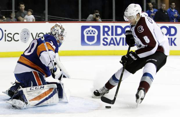 Colorado Avalanche's Joe Colborne (8) drives toward New York Islanders goalie Jean-Francois Berube (30) during the first period of an NHL hockey game Sunday, Feb. 12, 2017, in New York. Colborne scored a goal on the play. (AP Photo/Frank Franklin II)