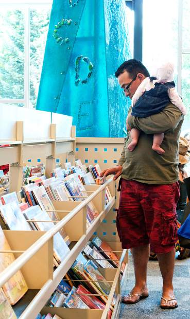 A father and his baby browse the shelves in the children's area of the Carbondale Branch Library.