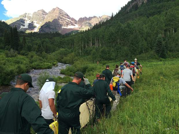 Cadets and Forest Service employees carry a wooden beam up to the construction site of a new foot bridge in the Maroon Bells-Snowmass Wilderness,