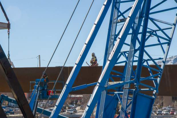 Crews work to place the first steel girder for the north side of the Grand Avenue traffic bridge.