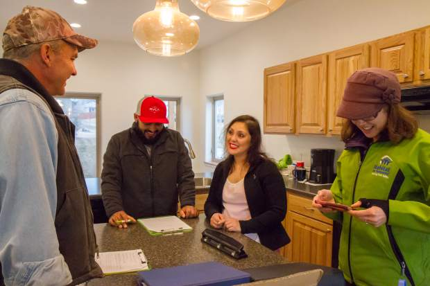Adrian Torres and Laura Munoz, center, go over a checklist during the tour of their new home with construction supervisor Rick Farr and Habitat for Humanity volunteer coordinator Amy French.