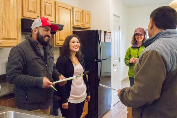Adrian Torres and Laura Munoz go through a check list during a walk-through of their new Silt home, which they will soon be moving into with their four children.