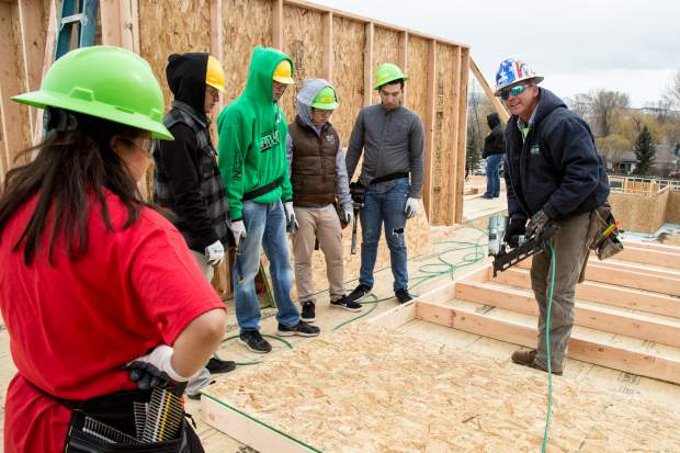 Habitat for Humanity Site Superintendent, Rick Farr, teaches the volunteers how to use the nail gun to attach the plywood to the outside wall of the two story duplex in Silt.