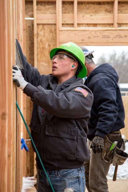Second semester CMC Rifle student, Jesus Raygoza, nails a stud into one of the walls in a Habitat for Humanity duplex being built in Silt.