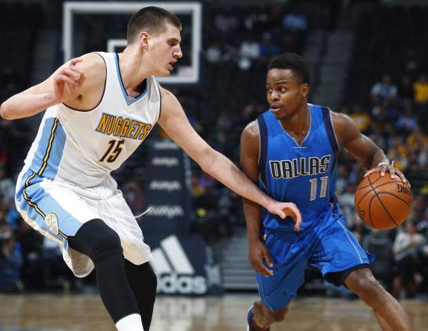 Denver Nuggets forward Nikola Jokic, left, of Serbia, defends as Dallas Mavericks guard Yogi Ferrell drives to the net in the first half of an NBA basketball game, Monday, Feb. 6, 2017, in Denver. (AP Photo/David Zalubowski)