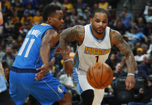 Dallas Mavericks guard Yogi Ferrell, left, pursues a loose ball with Denver Nuggets guard Jameer Nelson in the second half of an NBA basketball game, Monday, Feb. 6, 2017, in Denver. The Nuggets won 110-87. (AP Photo/David Zalubowski)