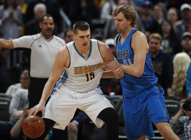 Denver Nuggets forward Nikola Jokic, left, of Serbia, tries to work the ball inside for a shot as Dallas Mavericks forward Dirk Nowitzki, of Germany, defends in the first half of an NBA basketball game Monday, Feb. 6, 2017, in Denver. (AP Photo/David Zalubowski)