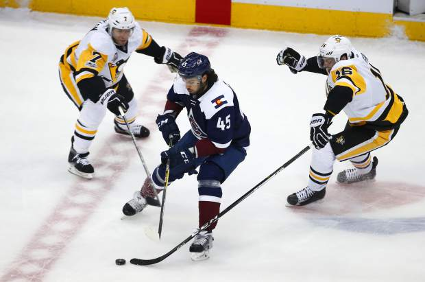 Colorado Avalanche defenseman Mark Barberio (45) slips between Pittsburgh Penguins center Matt Cullen (7) and Eric Fehr (16) during the first period of an NHL hockey game, Thursday, Feb. 9, 2017, in Denver. (AP Photo/Jack Dempsey)