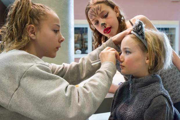 Eleven-year-old Bella Brown, left, helps Louisa Wren with her makeup before their performance in Cirque d'Sopris Sunday.