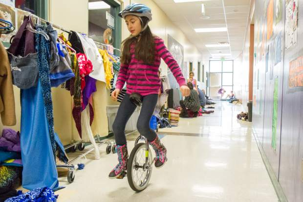 A student rides a unicycle past a row of costumes before Cirque d'Sopris Sunday.