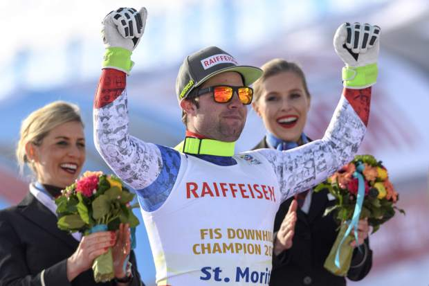 Beat Feuz of Switzerland celebrate on the podium during the Winner's Presentation in the finish area after during the men's downhill race at the 2017 FIS Alpine Skiing World Championships in St. Moritz, Switzerland, Sunday, Feb. 12, 2017. (Peter Schneider/Keystone via AP)