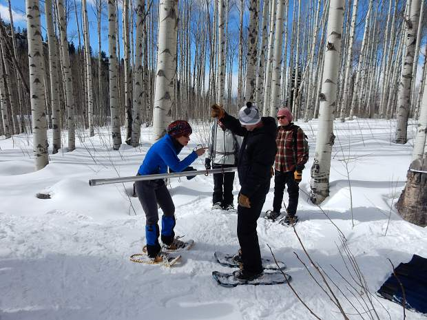 Derrick Wyle (right) measures instruments to gauge the snow water equivalent in the snowpack atop McClure Pass on Sunday. He is assisted by Frances Bogle of Marble.