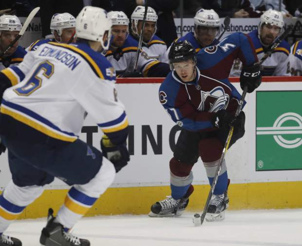 Colorado Avalanche left wing J.T. Compher, back, drives down the ice with the puck as St. Louis Blues defenseman Joel Edmundson drops back to defend in the first period of an NHL hockey game, Sunday, March 5, 2017, in Denver. (AP Photo/David Zalubowski)