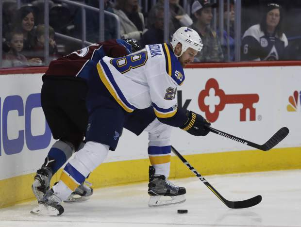 St. Louis Blues center Kyle Brodziak, front, runs Colorado Avalanche left wing Matt Nieto into the boards to take control of the puck in the first period of an NHL hockey game, Sunday, March 5, 2017, in Denver. (AP Photo/David Zalubowski)