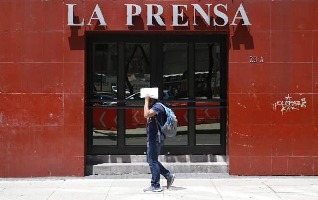A man shields his face from the sun as he walks past the offices of tabloid newspaper La Prensa on Paseo de la Reforma in Mexico City, Monday, March 20, 2017. The mystery of Tom Brady's missing Super Bowl jersey led police all the way to Mexico, and authorities were investigating a former tabloid newspaper executive's possible role in the case.(AP Photo/Rebecca Blackwell)