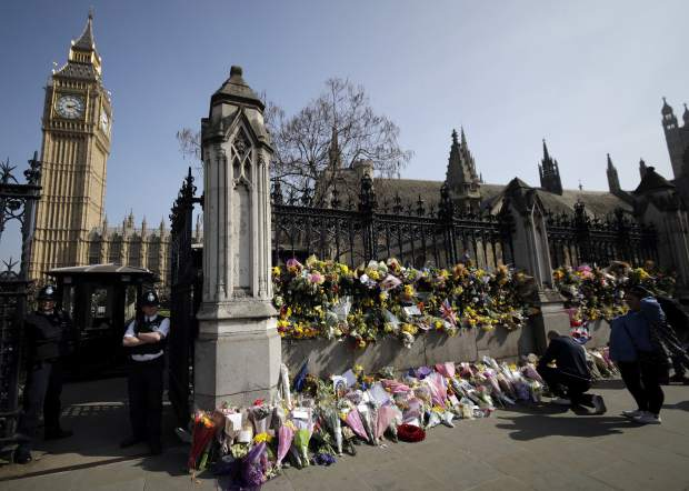People look at the floral tributes placed for the victims of the Westminster terrorist attack, outside the Palace of Westminster, London, Monday March 27, 2017. Attacker Khalid Masood is believed to have used the messaging service WhatsApp before running down pedestrians on Westminster Bridge and storming a gate outside Parliament armed with two knives, Wednesday. Four died in the rampage, including a police officer. (AP Photo/Matt Dunham)