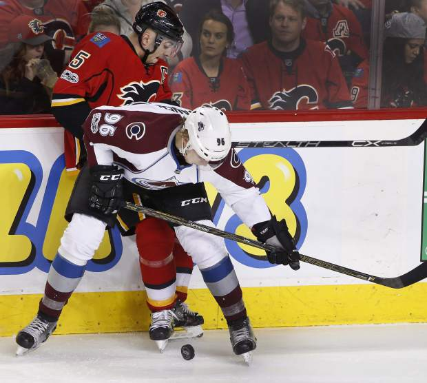 Colorado Avalanche's Mikko Rantanen, bottom, from Finland, battles for the puck with Calgary Flames' Mark Giordano during second period NHL action in Calgary, Alberta, Monday, March 27, 2017. (Larry MacDougal/The Canadian Press via AP)