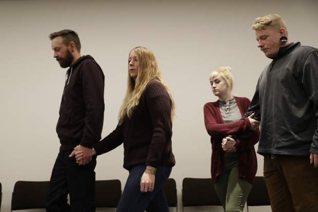 Dallas Cochran, right, the son of Kurt Cochran who was killed in Wednesday's London attack, walks away at the end of a family press conference with his partner Cheyenne Peck, second right, and the brother of Kurt's wife Melissa, who was injured in the attack, Michael Payne, left, with his wife Shantell Payne, second left, at New Scotland Yard, the headquarters of the Metropolitan Police force, in London, Monday, March 27, 2017. (AP Photo/Matt Dunham)