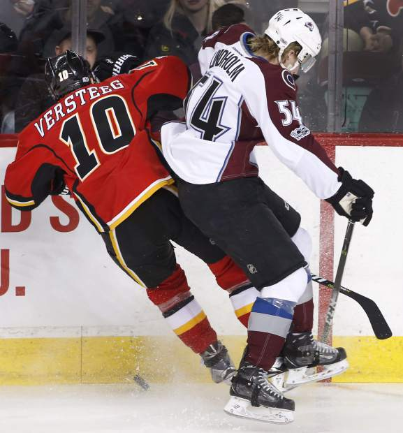 Colorado Avalanche's Anton Lindholm, right, from Sweden, battles for the puck with Calgary Flames' Kris Versteeg during second period NHL action in Calgary, Alberta, Monday, March 27, 2017. (Larry MacDougal/The Canadian Press via AP)