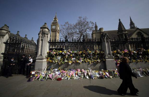 People pass by the floral tributes placed for the victims of the Westminster terrorist attack, outside the Palace of Westminster, London, Monday March 27, 2017. Attacker Khalid Masood is believed to have used the messaging service WhatsApp before running down pedestrians on Westminster Bridge and storming a gate outside Parliament armed with two knives, Wednesday. Four died in the rampage, including a police officer. (AP Photo/Matt Dunham)