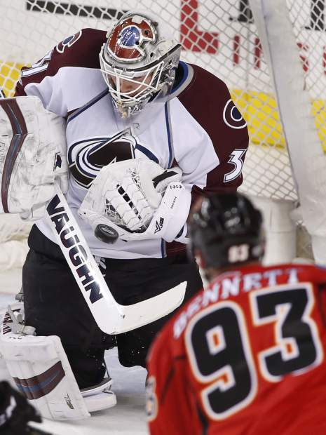 Colorado Avalanche goalie Calvin Pickard, left, makes a save against Calgary Flames' Sam Bennett during second period NHL action in Calgary, Alta., Monday, March 27, 2017. (Larry MacDougal/The Canadian Press via AP)