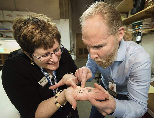 Susie Moss, (left) development manager of the Denver Museum of Nature & Science, and James Hagadorn examine micro diamonds in the museum's geology lab.