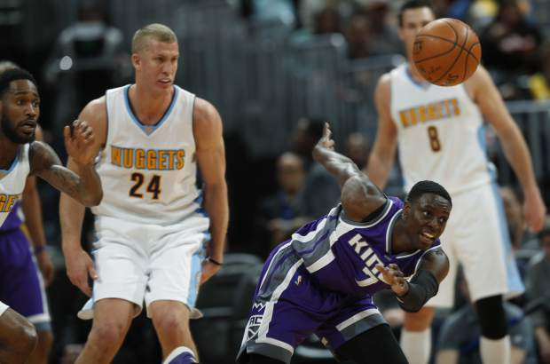 Sacramento Kings guard Darren Collison, right, loses control of the ball as he drives past Denver Nuggets guard Will Barton, left, and center Mason Plumlee in the first half of an NBA basketball game, Monday, March 6, 2017, in Denver. (AP Photo/David Zalubowski)
