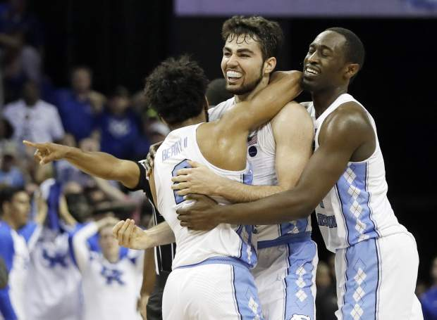 North Carolina forward Luke Maye, center, celebrates with teammates after shooting the winning basket in the second half of the South Regional final game against Kentucky in the NCAA college basketball tournament Sunday, March 26, 2017, in Memphis, Tenn. The basket gave North Carolina a 75-73 win. (AP Photo/Mark Humphrey)